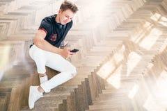 Młody człowiek używa jego smartphone z hełmofonami, słucha muzykę i siedzi na podłoga obraz royalty free