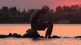 Młody człowiek używa laptop na seashore Freelance poj?cie Technologia i podr?? Praca sen w na wolnym powietrzu Freelancer mężczyz zbiory wideo