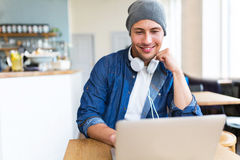 Młody człowiek używa laptop przy kawiarnią Fotografia Stock