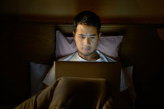 Młody człowiek używa laptop w jego łóżku fotografia royalty free