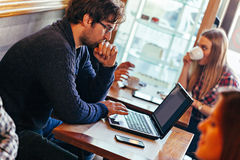 Młody Człowiek Używa laptop W kawiarni Zdjęcia Royalty Free