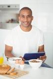Młody człowiek używa pastylkę i jedzący śniadanie w kuchni Fotografia Royalty Free