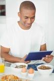 Młody człowiek używa pastylkę i jedzący śniadanie w kuchni Zdjęcie Stock