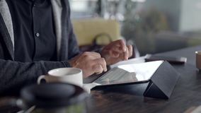 Młody człowiek używa pastylka komputer i pijący herbaty w kawiarni zbiory wideo