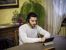 Młody człowiek używa pastylka peceta oglądać wideo lub film obrazy royalty free