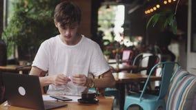 Młody człowiek używa słuchawki z drutami spisywać muzykę w kawiarni, nowożytny pracującego miejsca obsiadanie w kawiarni Otwiera  zbiory wideo