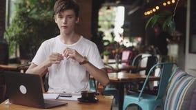 Młody człowiek używa słuchawki z drutami spisywać muzykę w kawiarni, nowożytny pracującego miejsca obsiadanie w kawiarni Otwiera  zbiory
