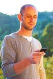 Młody człowiek używa smartphone plenerowego Zdjęcie Royalty Free