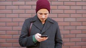 Młody człowiek używa smartphone pozycję ściana z cegieł w mieście zdjęcie wideo
