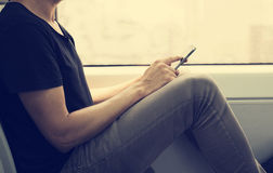 Młody człowiek używa smartphone w pociągu lub metrze Zdjęcie Stock