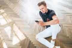 Młody człowiek używa smartphone z hełmofonami, słucha muzykę i obrazy stock