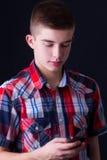 Młody człowiek używa telefon komórkowego Fotografia Royalty Free