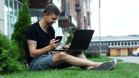 Młody człowiek używa telefon komórkowego i laptop podczas gdy siedzący na trawie zbiory