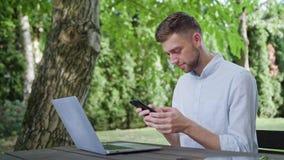 Młody człowiek używa telefon w parku zdjęcia royalty free