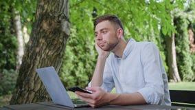 Młody człowiek używa telefon w parku fotografia stock