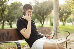 Młody człowiek używa telefonu obsiadanie na parkowej ławce obraz stock