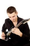 Młody człowiek ubierający w czerni ubraniach siedzi gitarę i bawić się Obraz Stock