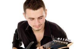 Młody człowiek ubierający w czerni ubraniach siedzi gitarę i bawić się Obraz Royalty Free