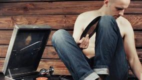 Młody człowiek udaje słuchać stary gramofon w domu zdjęcie wideo
