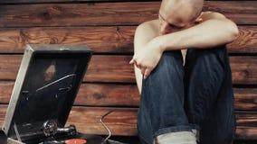 Młody człowiek udaje słuchać stary gramofon w domu zbiory wideo