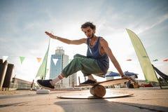 Młody człowiek utrzymuje balansowym na tle miasto budynki fotografia royalty free