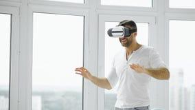 Młody człowiek VR doświadczenie z rzeczywistości wirtualnej słuchawki używać ręka gesty dla kontrola Zdjęcia Stock