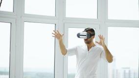 Młody człowiek VR doświadczenie z rzeczywistości wirtualnej słuchawki używać ręka gesty dla kontrola Zdjęcie Royalty Free