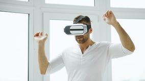 Młody człowiek VR doświadczenie z rzeczywistości wirtualnej słuchawki używać ręka gesty dla kontrola Obraz Stock