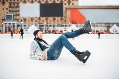 Młody człowiek w łyżwach siedzi na lodzie, łyżwiarski lodowisko zdjęcie stock