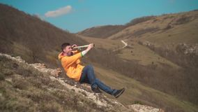 Młody człowiek w żółtej kurtce, niebiescy dżinsy siedzi na skale i spojrzeniach przez pary spyglass, teleskop zdjęcie wideo