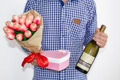 Młody człowiek w błękitnej szkockiej kraty koszula, cajgach trzyma i, bukiet tulipany, sercowatego prezenta pudełko i butelkę win fotografia royalty free
