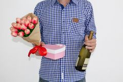 Młody człowiek w błękitnej szkockiej kraty koszula, cajgach trzyma i, bukiet tulipany, sercowatego prezenta pudełko i butelkę win zdjęcie stock