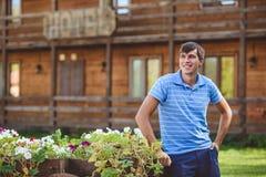 Młody człowiek w błękitnym błękicie i koszula zwiera blisko dekoracyjnych drewnianych fur z kwiatami, na tle wieśniaka styl Fotografia Stock