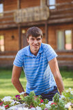 Młody człowiek w błękitnym błękicie i koszula zwiera blisko dekoracyjnych drewnianych fur z kwiatami, na tle wieśniaka styl Obraz Royalty Free
