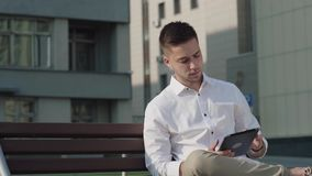 Młody człowiek w białej przypadkowej koszula z pastylka komputerem w ulicie zdjęcie wideo