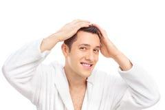 Młody człowiek w białym bathrobe robi jego włosy Zdjęcie Stock