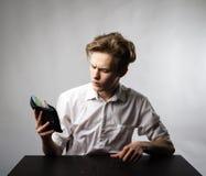 Młody człowiek w bielu i portfel z dwadzieścia euro fotografia stock