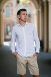 Młody człowiek w bielu koszulowych beżowych breeches trzyma jego ręki w kieszeniach na kolorowym zamazanym tle obrazy royalty free