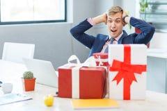 Młody człowiek w biurze otrzymywa prezent Fotografia Stock