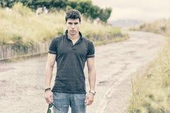 Młody człowiek w cajgach along i czarnym koszulki odprowadzeniu fotografia stock