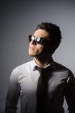 Młody człowiek w chłodno okularach przeciwsłonecznych odizolowywających na szarość Zdjęcia Royalty Free