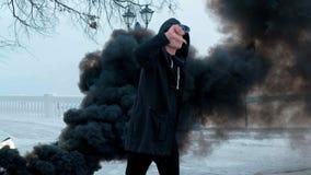 Młody człowiek w czarnej kurtce czyta rap na tle drogi biały carthe skutek czerń dym zdjęcie wideo