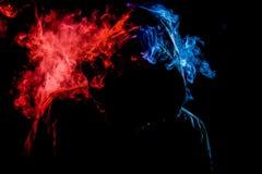 Młody człowiek w czarnym kapiszonie dymi fotografia royalty free