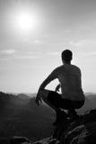 Młody człowiek w czerń sportów spodniach i popielatej koszula jest siedzący na falezy krawędzi i patrzeć mglisty dolinny bellow Fotografia Stock