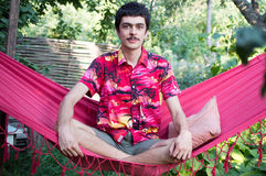Młody człowiek w czerwonym hamaku Zdjęcia Royalty Free