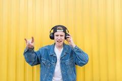 Młody człowiek w drelichowej kurtce słucha kołysać w jego hełmofonach i pokazuje znaka ciężki metal zdjęcia royalty free