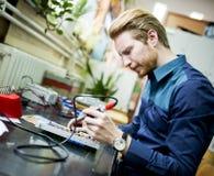 Młody człowiek w elektronika warsztatowych zdjęcie stock