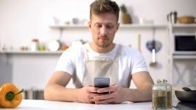 Młody człowiek w fartucha gmerania karmowym przepisie w telefonie komórkowym, porady w kulinarnych blogach zdjęcie royalty free