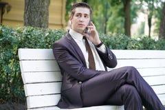 Młody człowiek w garniturze opuszczał biuro i przychodził park siedzi na białej ławce samotnie i opowiada na telefonie obraz royalty free