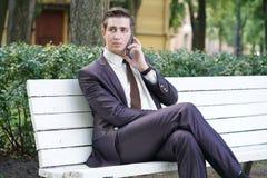 Młody człowiek w garniturze opuszczał biuro i przychodził park siedzi na białej ławce samotnie i opowiada na telefonie fotografia royalty free